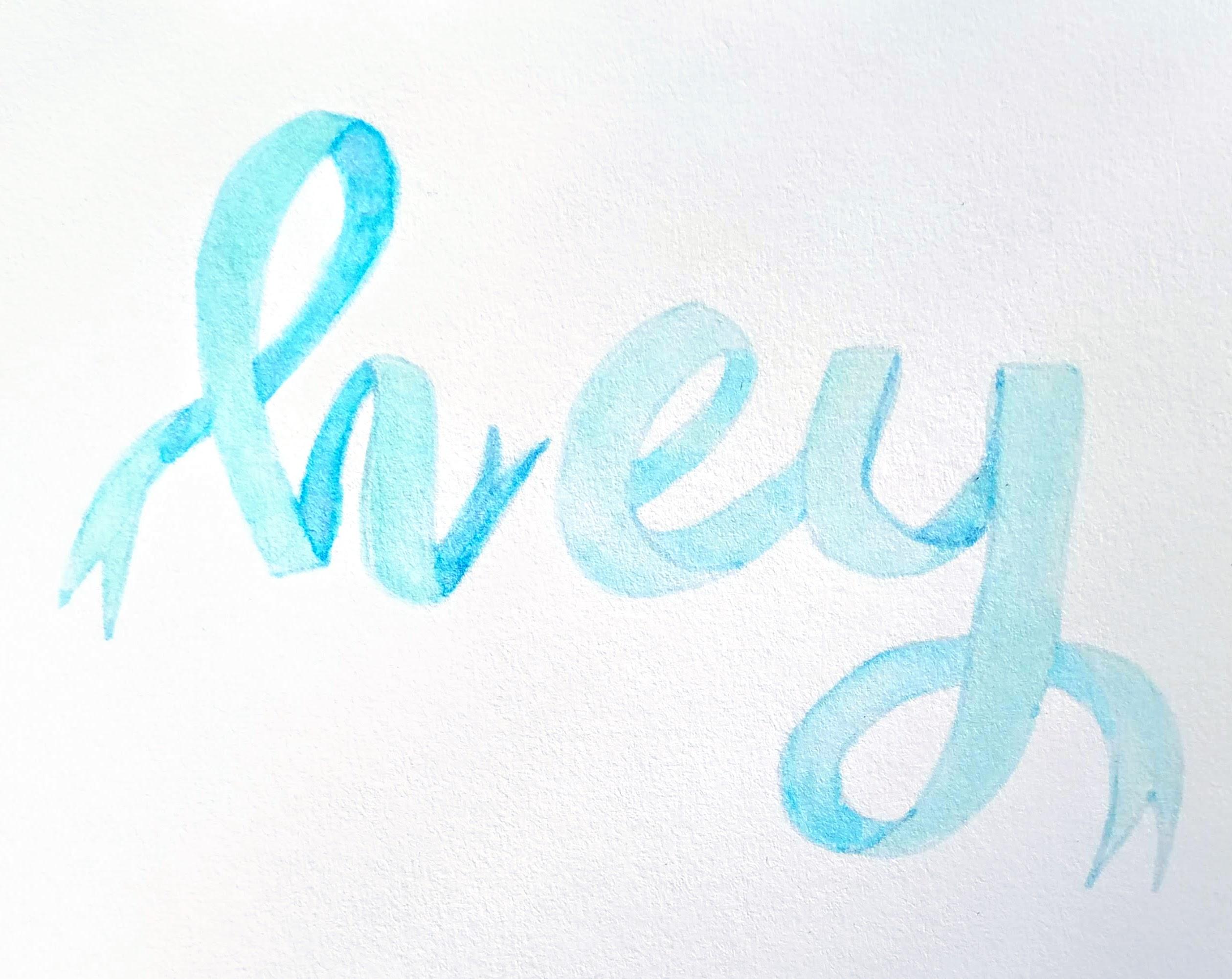 """Fertiges Ribbon Lettering auf Aquarell - Papier mit Tombow Brushpens in verschiedenen Blautönen kombiniert zum Wort """"hey"""", das aussieht als wäre es aus einem Ribbon gelettert."""