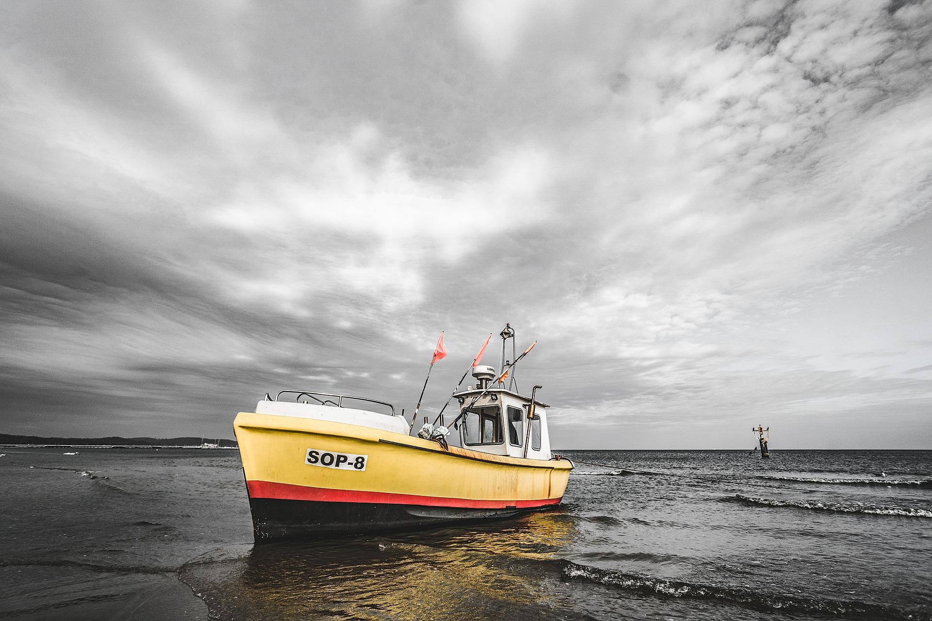 gelbes Boot vor grauem Himmel
