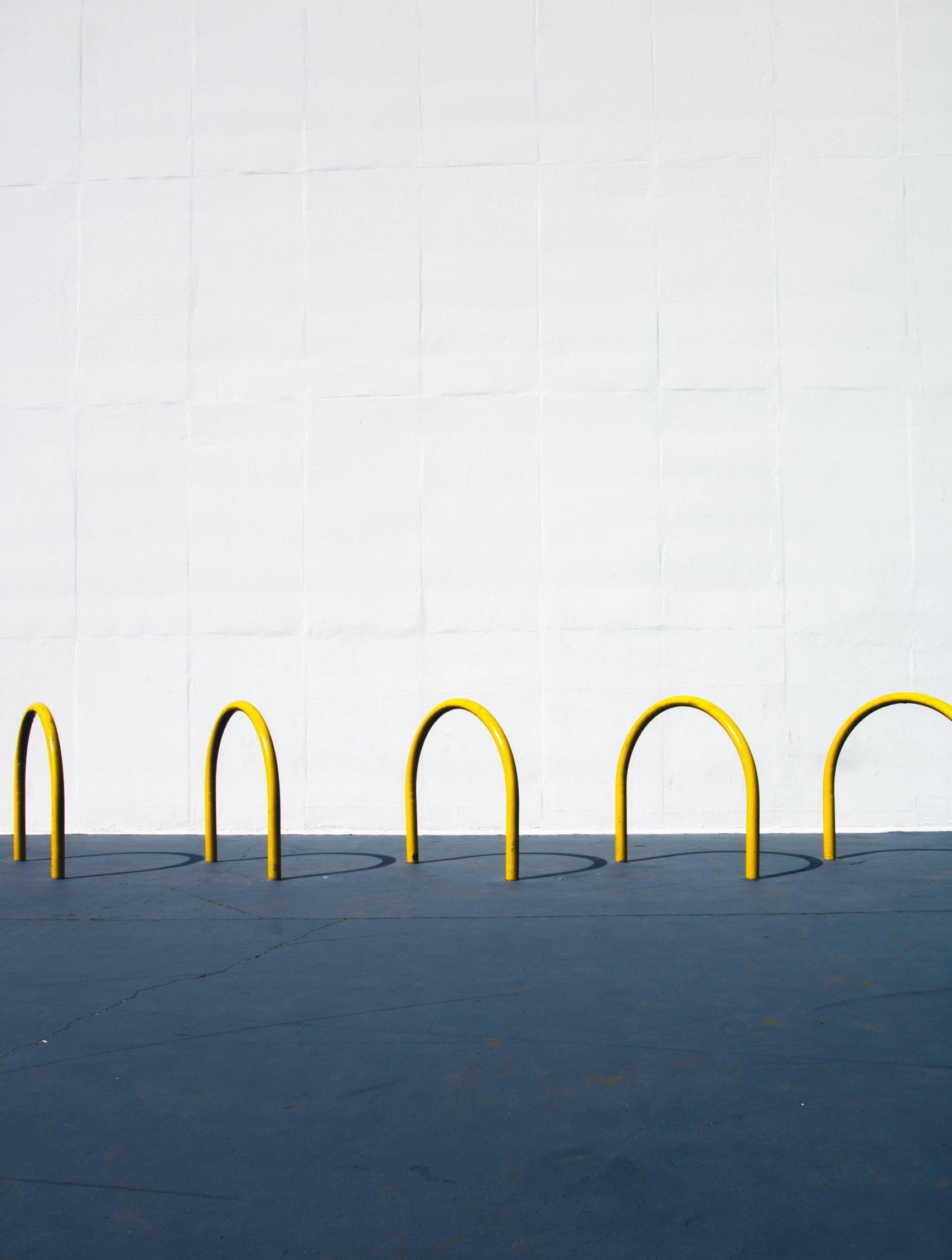 Gelbe Fahrradständer auf grauem Untergrund