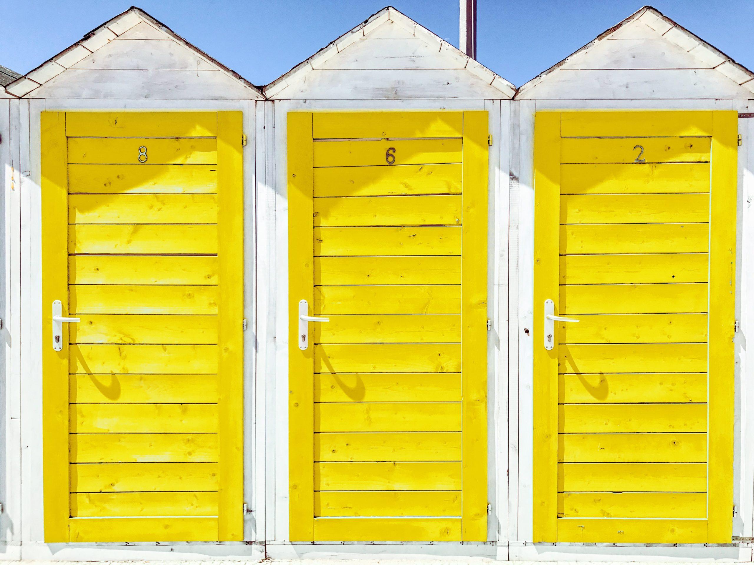 3 Srrandhäuser mit gelben Holztüren
