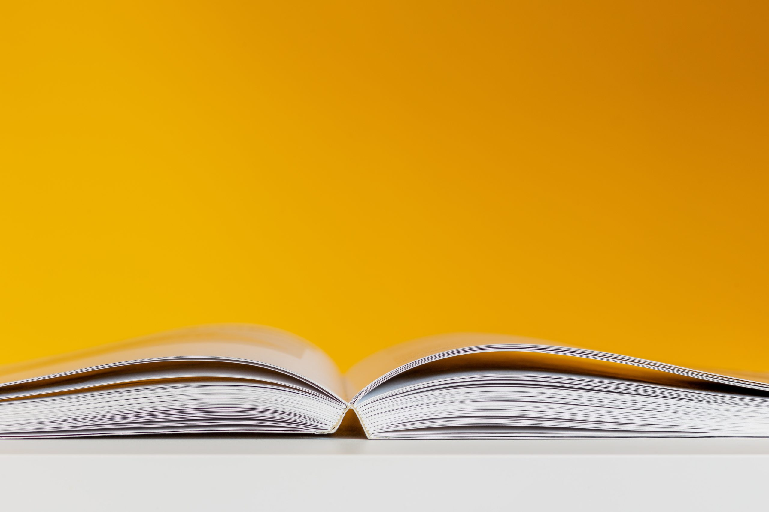 aufgeschlagenes Buch vor gelber Wand