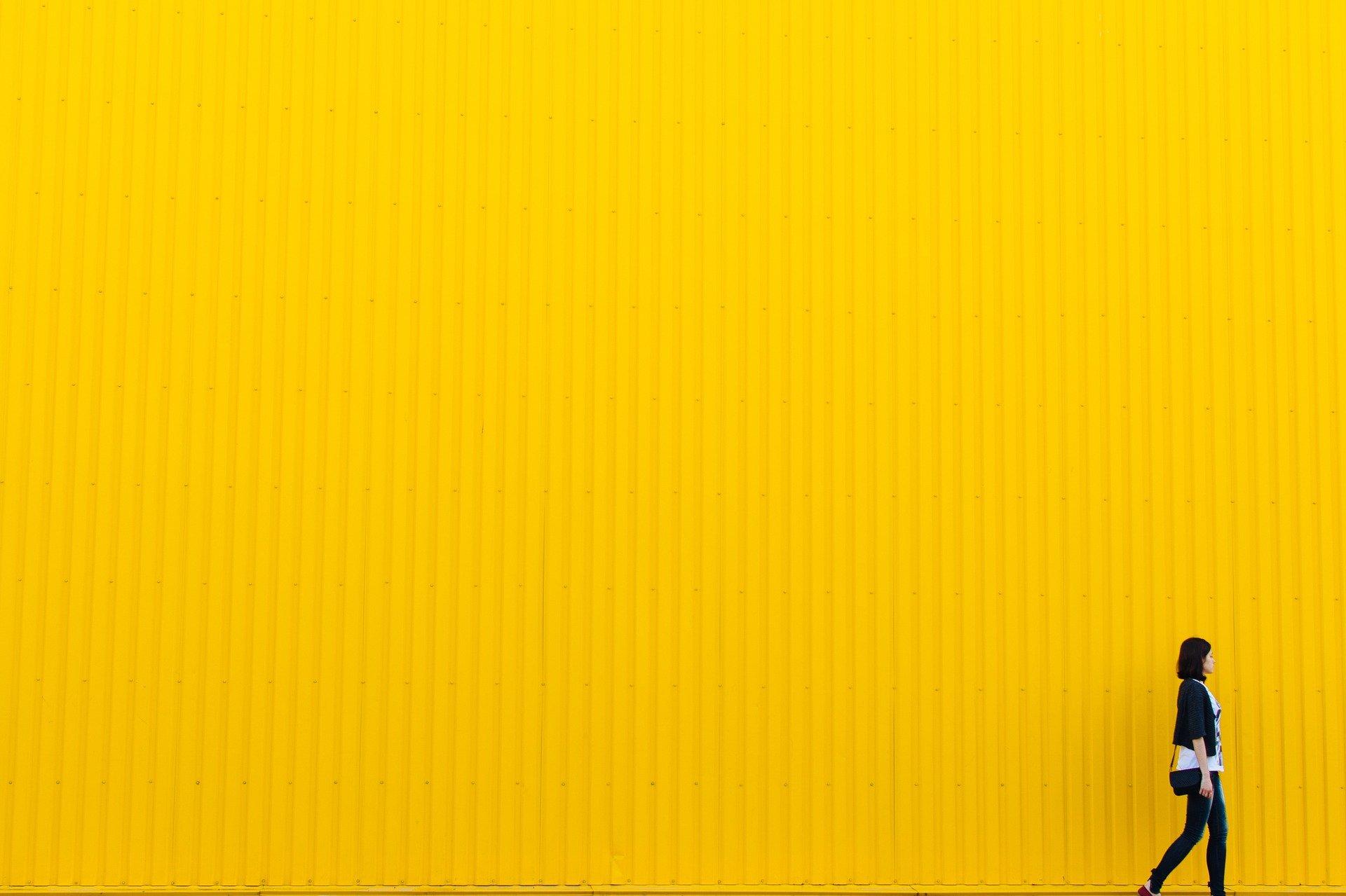 Mensch läuft vor gelber Wand