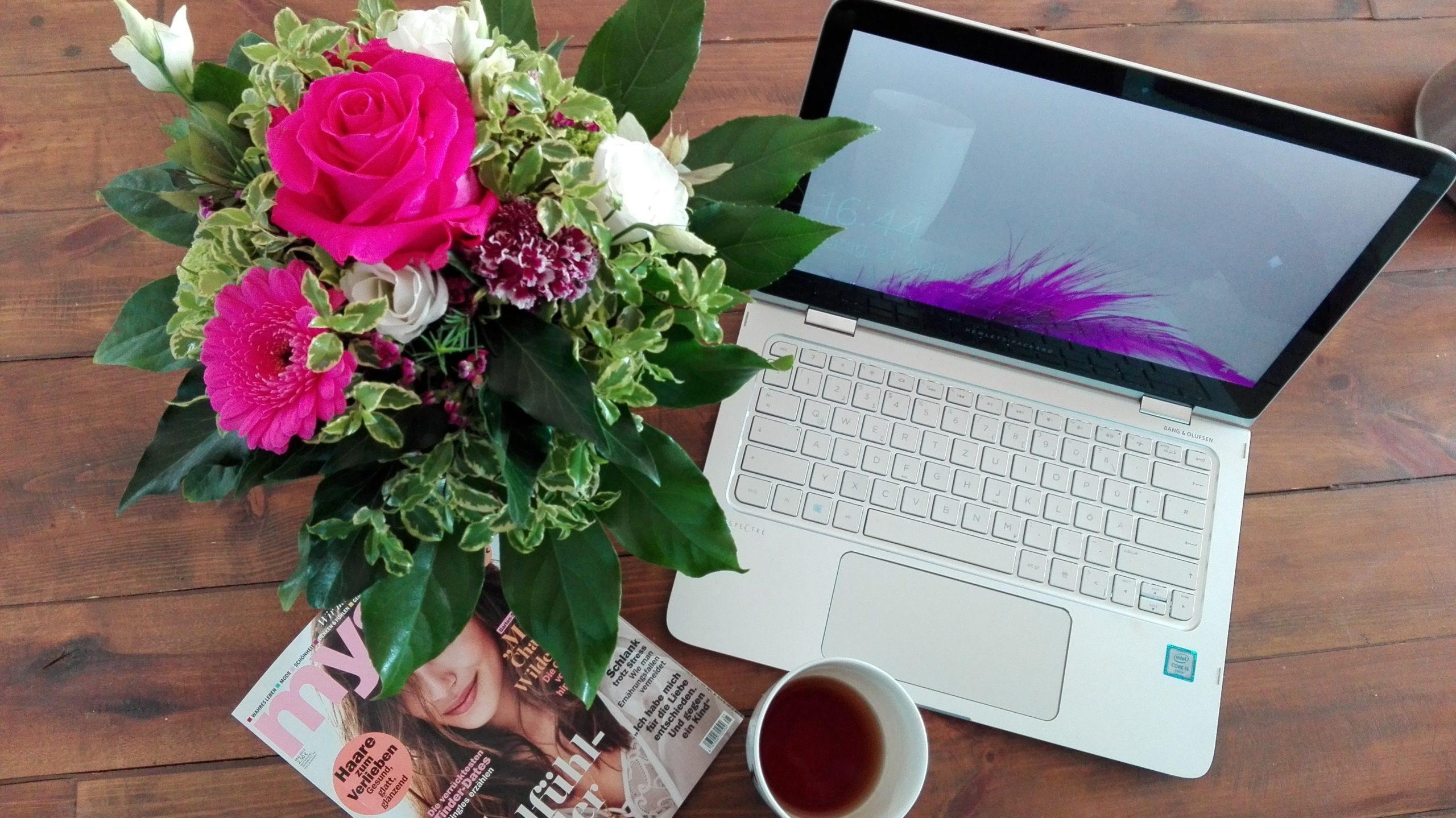Schoenes Flatlay mit Dingen aus dem Alltag: Laptop, Zeitschrift, Blumen